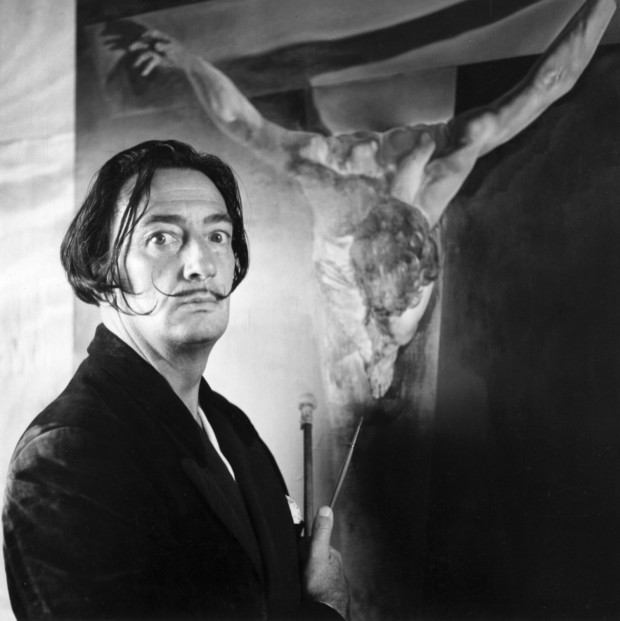 Featured Image: Spanish Surrealist painter Salvador Dalí in his studio in Port Lligat with his painting of Christ on the cross. salvador dali exhumed