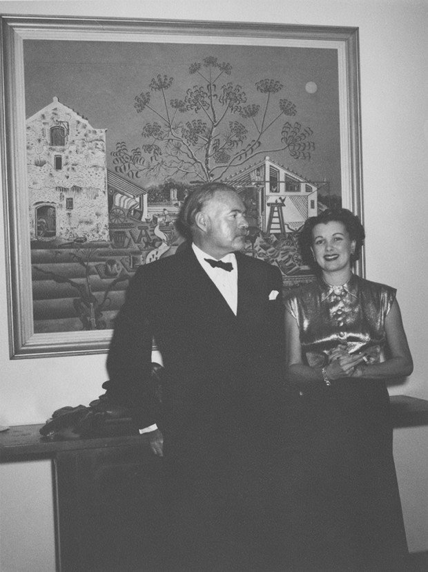 "Ernest Hemingway (in tuxedo) and unidentified in front of Miro's ""The Farm"" at Finca Vigia. Source: J.F.K Library Top and bottom borders of original print are not parallel, as reflected in this scan."