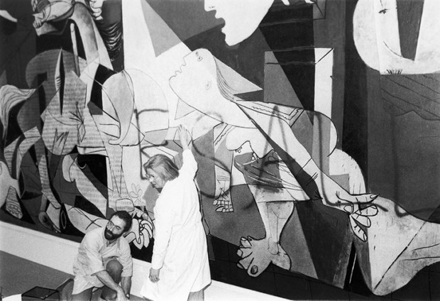 "art vandalism Modern Art employees clean spray paint off of Picasso's ""Guernica,"" after Tony Shafrazi vandalized it with the words ""Kill lies all,"" in February 1974."