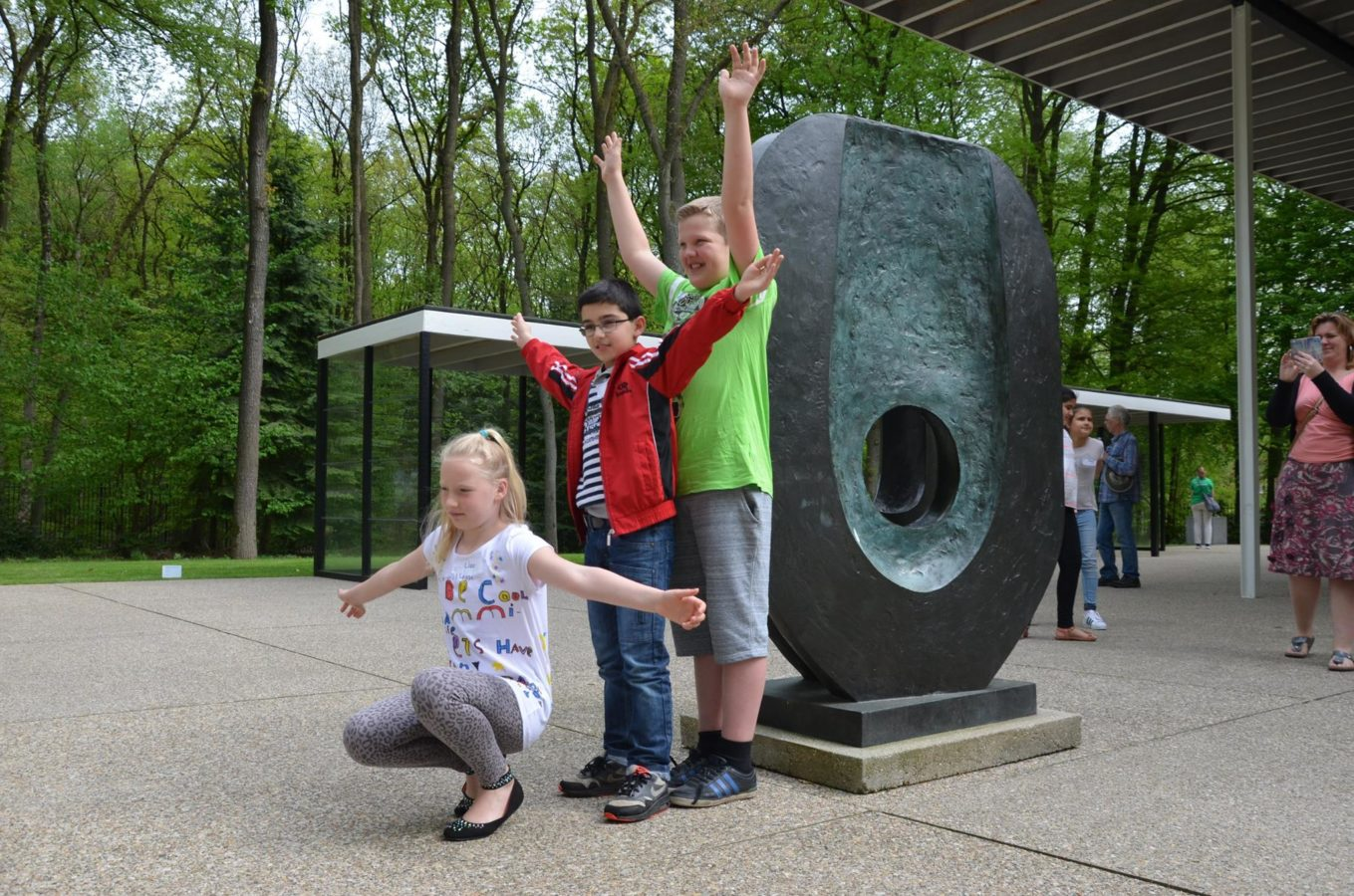 Children posing with Barbara Hepworth's Dual form, 1965 in the sculpture garden of the Kröller-Müller Museum.