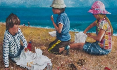 A group of young children eating chips at the seaside.
