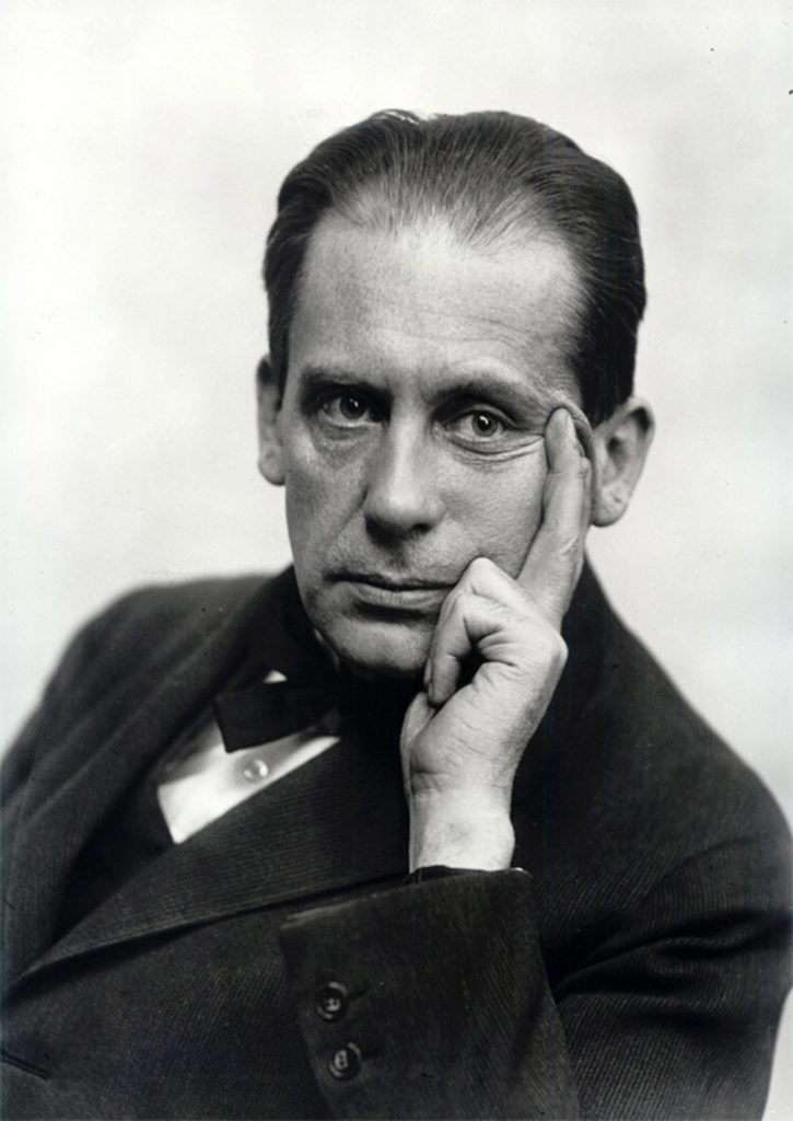 A portrait of an intense looking man, Walter Gropius, founder of the Bauhaus. He looks straight at the camera, his head supported in his hand.