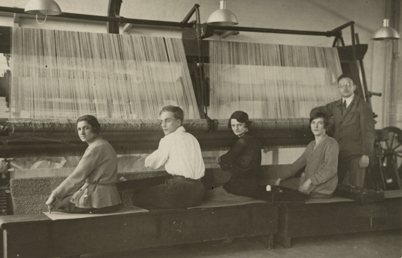 A group of people at looms in the Dessau Bauhaus, several women of the Bauhaus are pictured.