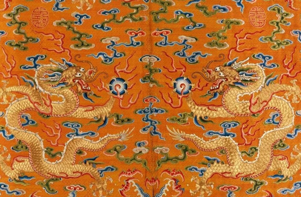 Fragment of the imperial Chinese New Year festival robe with two dragons and auspicious symbols on orange background.