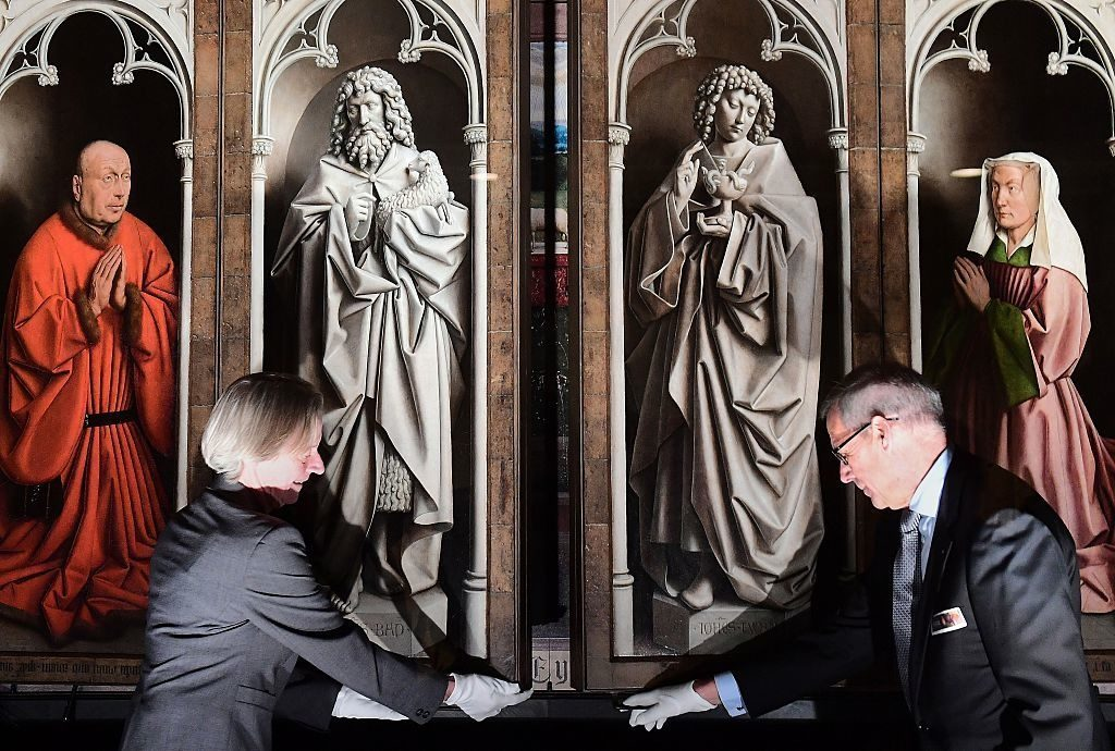"""Officials unveil the restored exterior panels of """"The Adoration of the Mystic Lamb"""" at Saint Bavo Cathedral in Ghent on October 12, 2016. Photo courtesy EMMANUEL DUNAND/AFP/Getty Images."""
