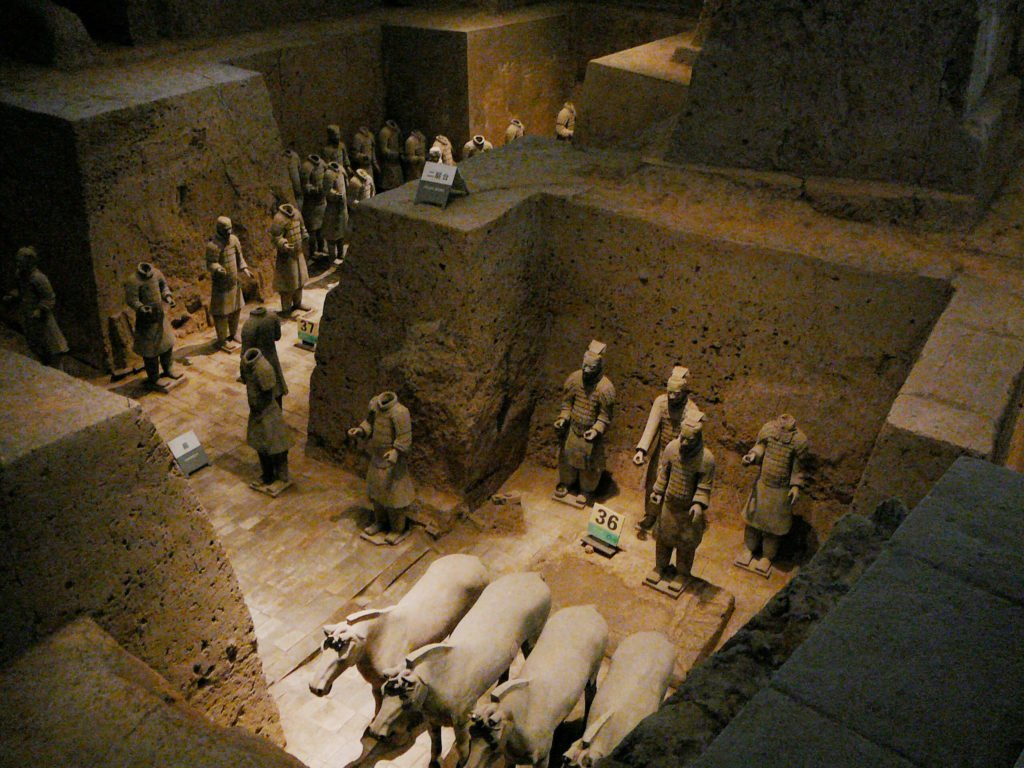 Many Terracotta Army warriors with and without their heads standing behind horses in Pit 2.