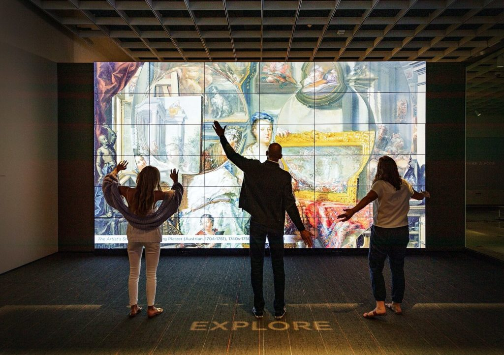 Two women and one man stretching their arms, interacting with a gesture-based ARTLENS display in the Cleveland Museum of Art.