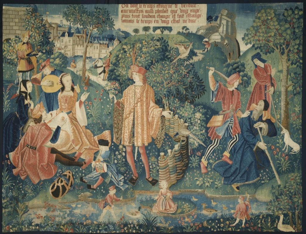 The scene from the French tapestry in the Cleveland Museum of Art with men and women in the foreground and trees, and houses in the background.