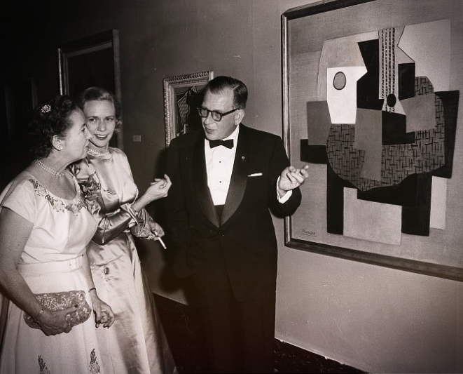 The woman, a critic of art, with her husband, an architect, stand in formal dresses in front of one of the Picasso's paintings and discussing it. The woman in the background listens to their conversation.