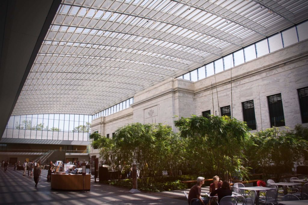 Atrium at the Cleveland Museum of Art with people sitting at the cafe table in the foreground, information desk in the background, sun lit through the glass roof.