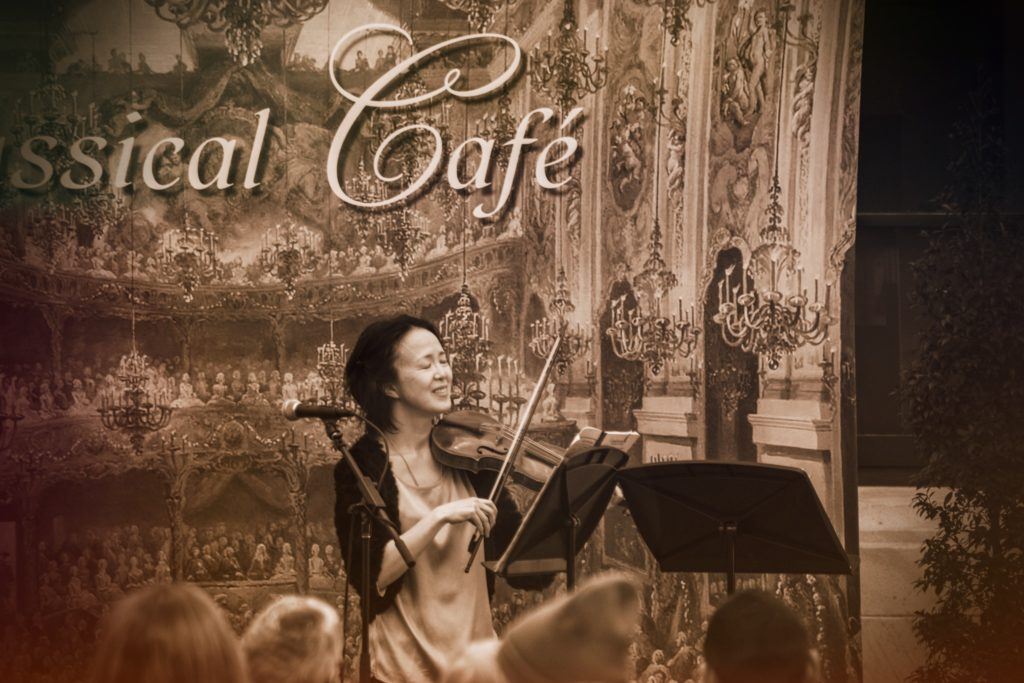The woman plays the violin in the Cleveland Museum of Art. The words Classical Café are written in the background of the scene.