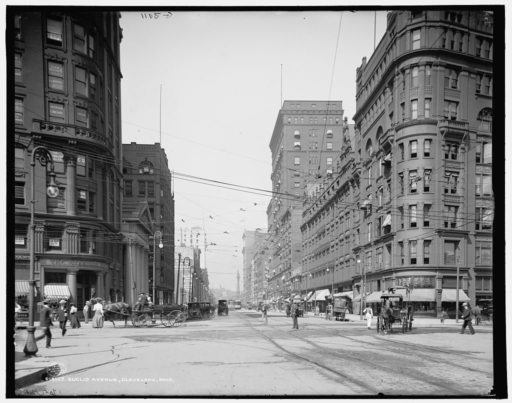 The street scene showing early 20th century Euclid Avenue in Cleveland, Ohio with people walking, horse carts and buildings on the both sides of the main road.