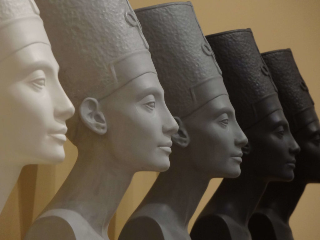 The replica of Nefertiti Busts in different gradations of color stand in a row