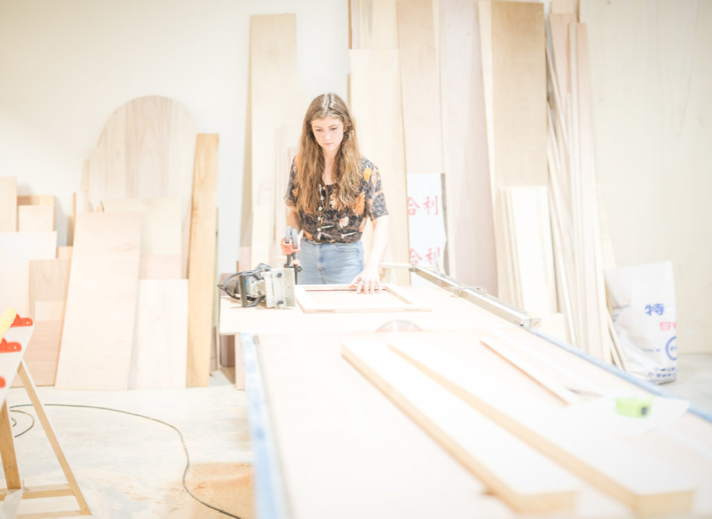 Photography of Emily Thomas, depicting a girl in a woodwork studio