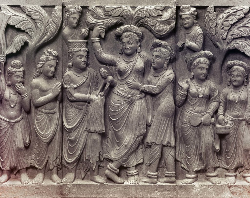 buddhist art, life of the buddha, stone relief with the woman standing in the centre surrounded by men and women