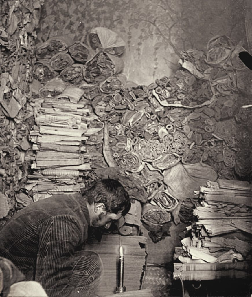 the man bending to examine manuscripts and scrolls in the dim cave