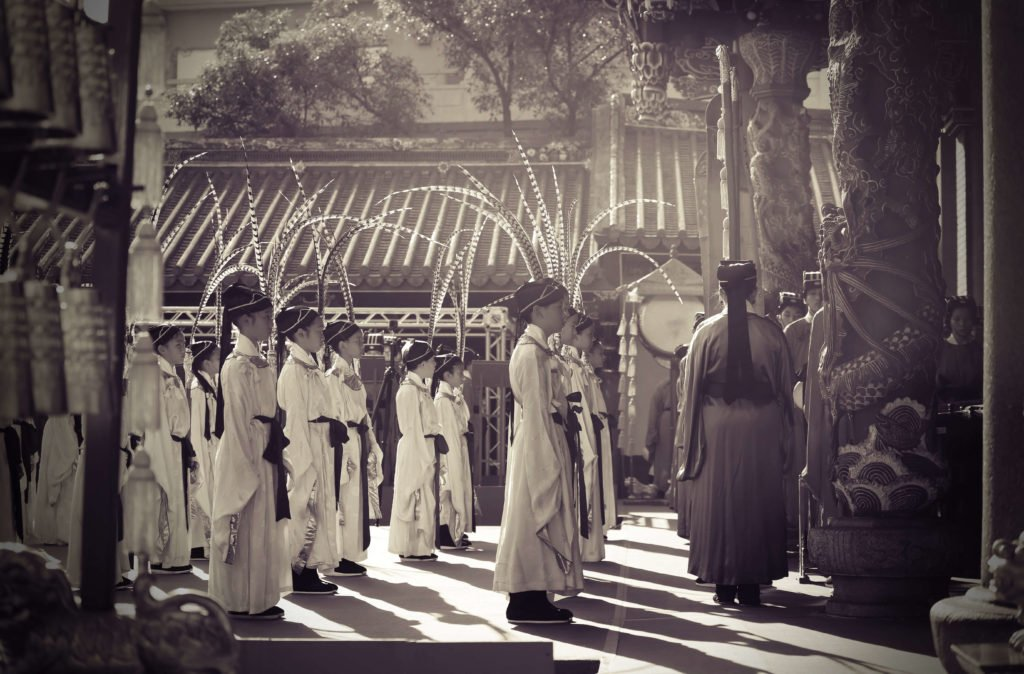 schoolchildren standing in a row in the traditional Chinese costumes in front of procession
