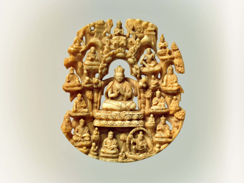 small round sculpture of the buddhist monk in the center surrounded by the figures of other monks