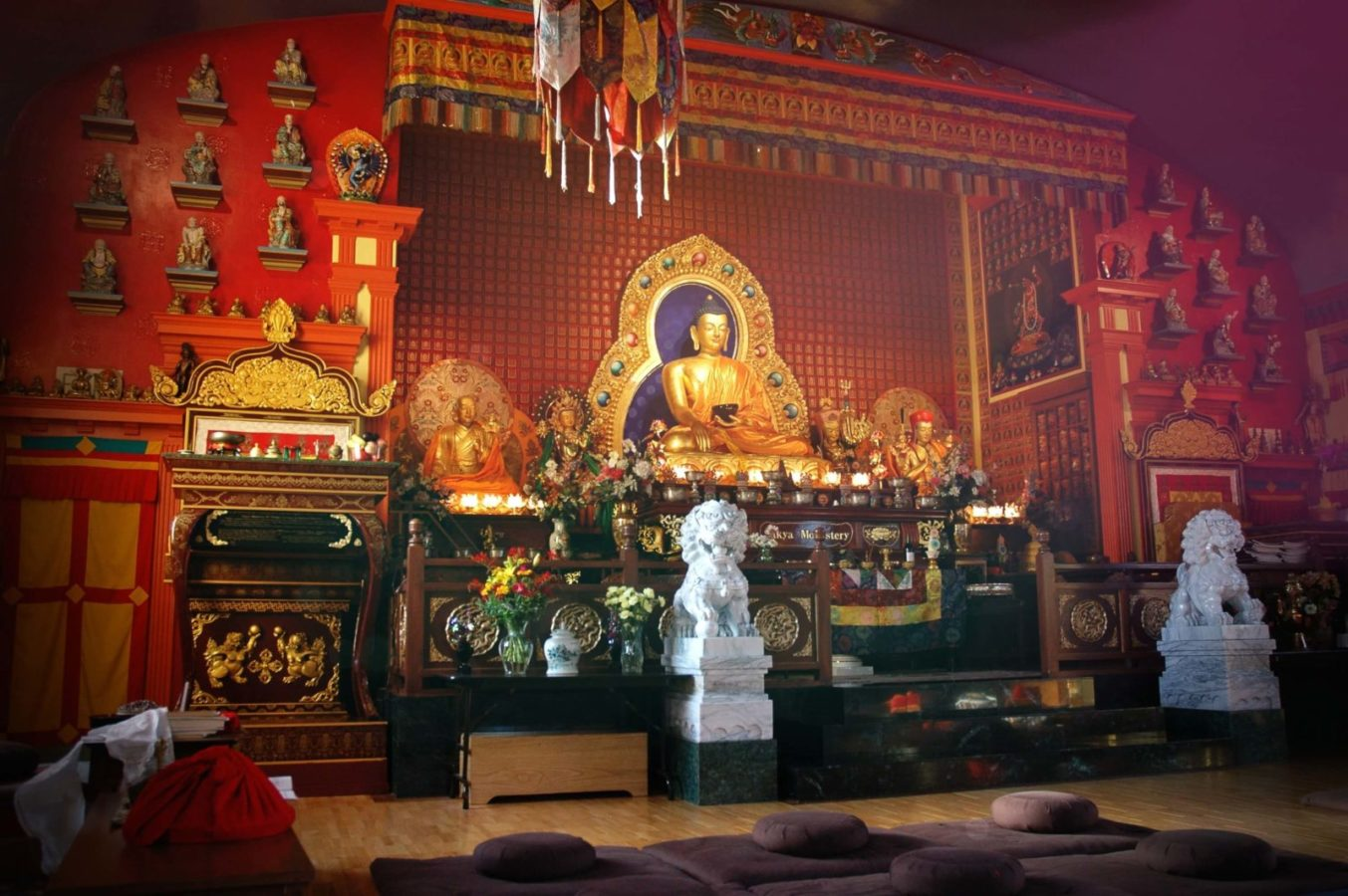 sculpture of the gilded buddha seated in the hall of the monastery surrounded by other deities