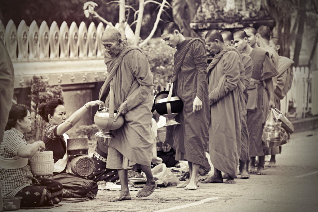 row of the monks standing with the alms bowl, two women sitting and giving them food