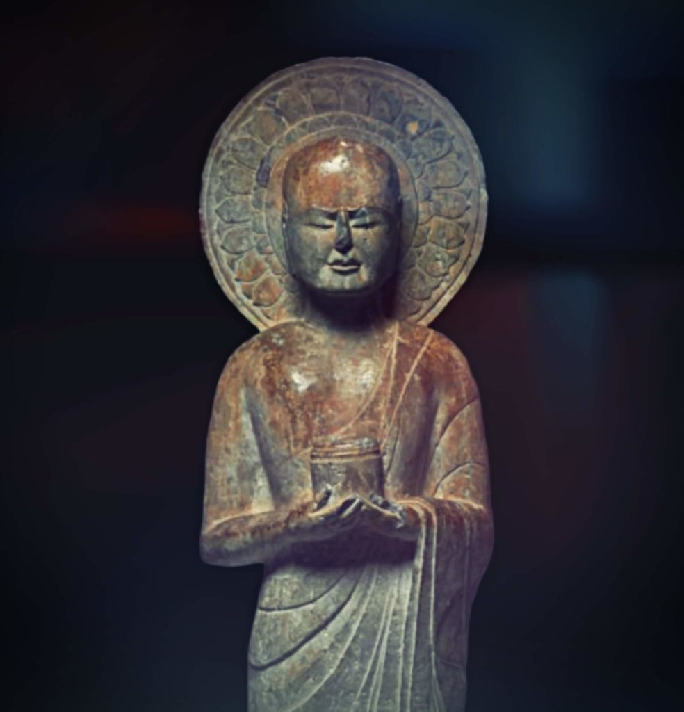 stone sculpture of the standing meditating monk with his eyes closed and container in his hands