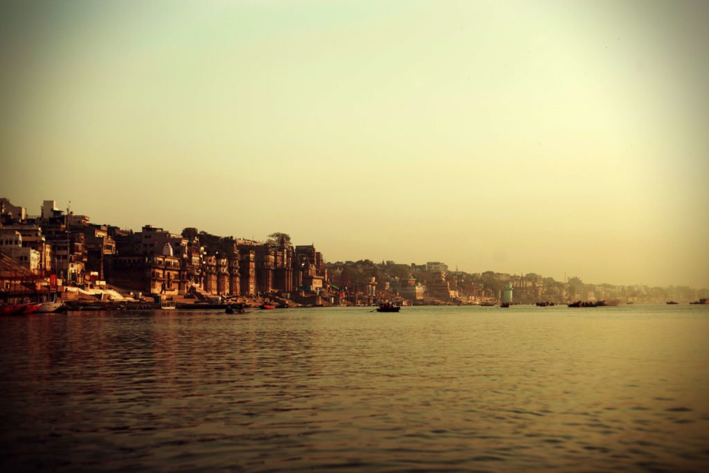 view of the city Varanasi with the river in the foreground and buildings in the background