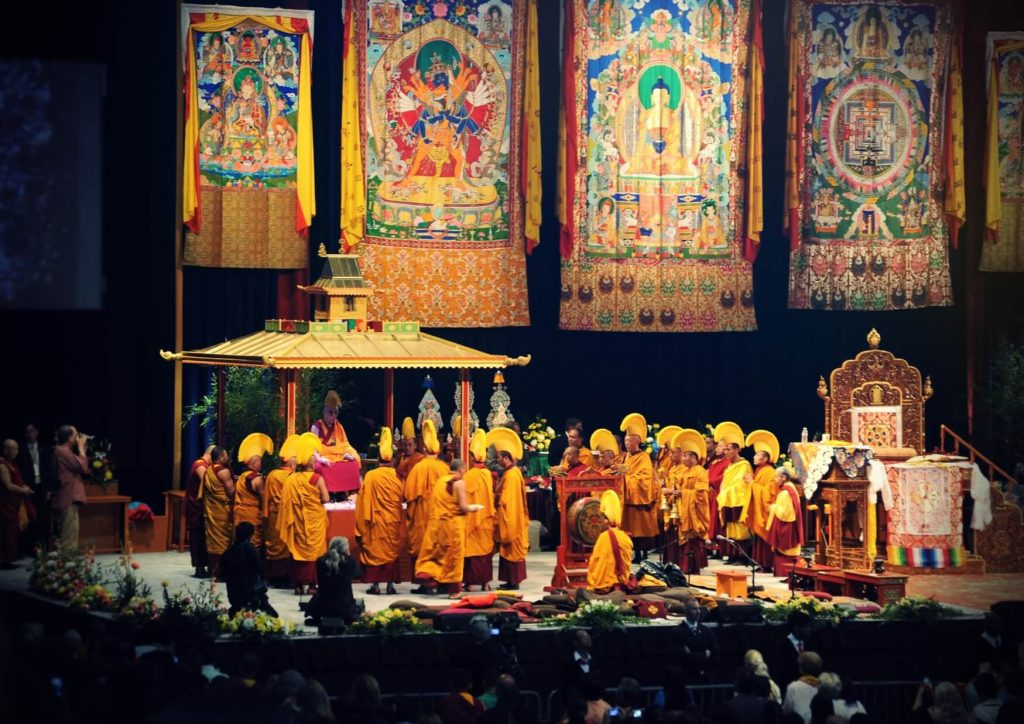 Dalai Lama in the yellow headdress in the center of the stage and monks surrounding him in the ceremony of the Kalachakra mandala with four paintings with mandalas and deities hanging above the group