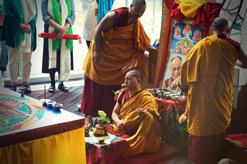 one Buddhist monk is sitting and meditating in front of the mandala, two other monks are standing, flanking the photo of Dalai Lama