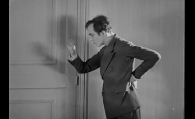 Frame of the Surrealist film, An Andalusian Dog. Pierre Batcheff's character is inside one apartment watching one of his hand