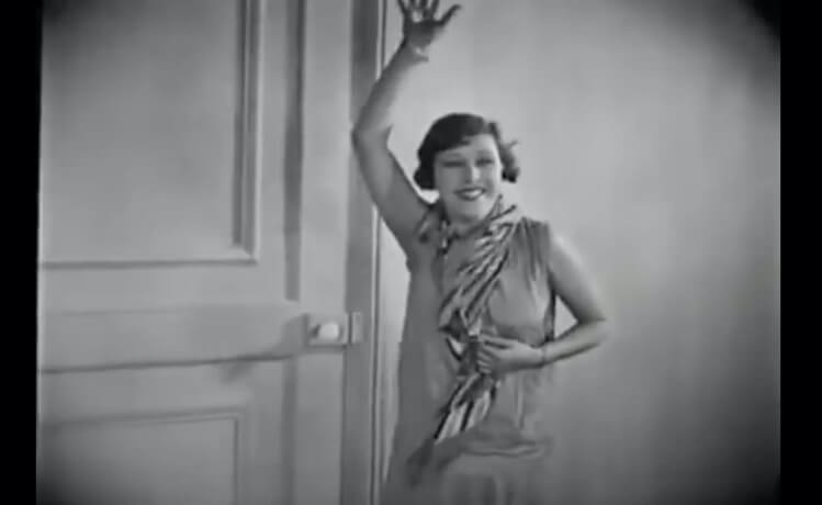 Frame of surrealist Film, An Andalusian Dog. Simone Mareuil Character is in front of a door she's waving and a breeze touches her face