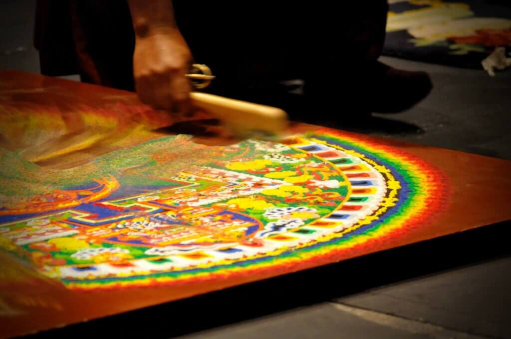 the monk is deconstructing the mandala, close-up