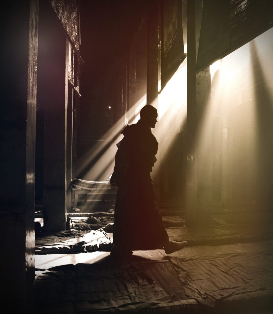 the monk walking inside the room towards the entrance lit with light