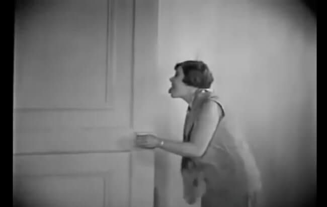 Frame of surrealist Film, An Andalusian Dog. Simone Mareuil Character is closing a door and showing her tong for where she was.