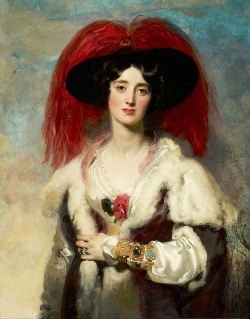 The portrait painting of Julia, Lady Peel by Sir Thomas Lawrence in the Frick Collection, New York, USA. The lady in the fanciful dress, hat with red feathers is standing and looking directly at us.