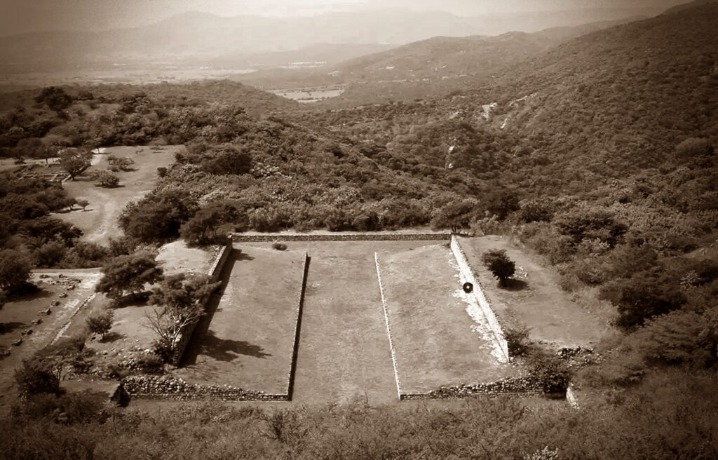 The remains of the main stone pitch for the ballgame in Mexico with the slanted platforms on both sides and view on the hills and trees