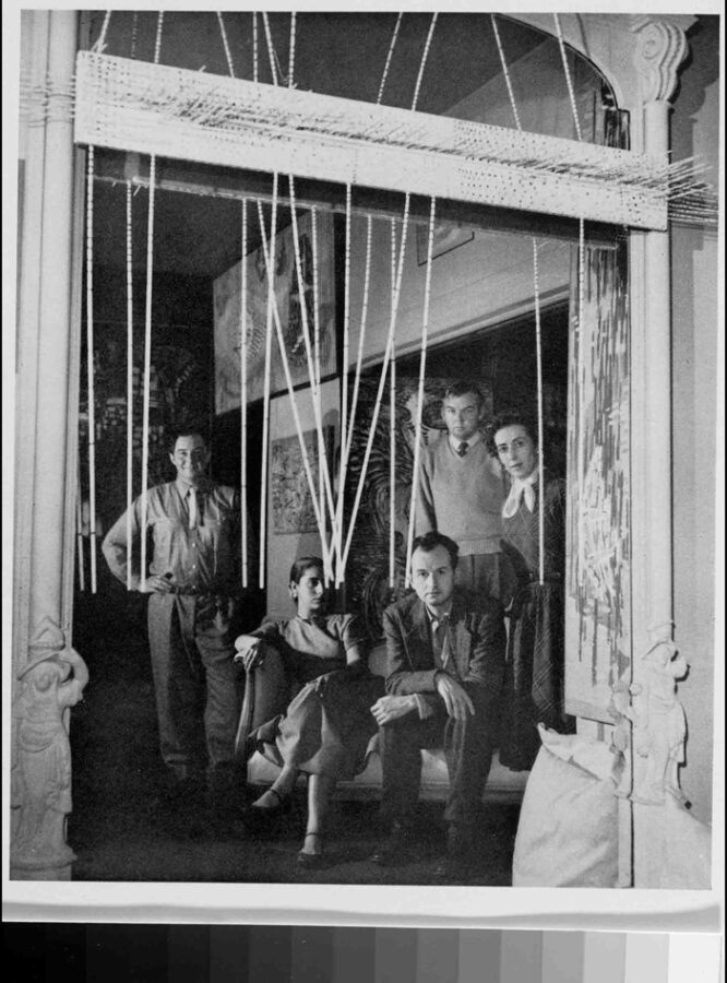 """Frontispiece of the Dynaton 1951 exhibition catalog. Left to right: Gordon Onslow Ford, Luchita Hurtado, Wolfgang Paalen, Lee Mullican, and Jacqueline Johnson in Onslow Ford's home on Telegraph Hill, San Francisco, 1949. (The suspended sculpture is one of Mullican's """"tactile ecstatics."""")"""