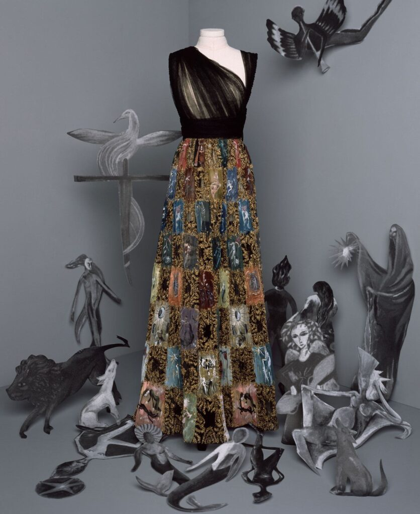 """Long black tulle dress. Asymmetrical draped bodice and skirt. It is embroidered with a multicolored chiffon checkerboard and painted with a Leonora Carrington """"Tarot"""" motif highlighted with gold thread. © Brigitte Niedermair, Courtesy of Dior."""