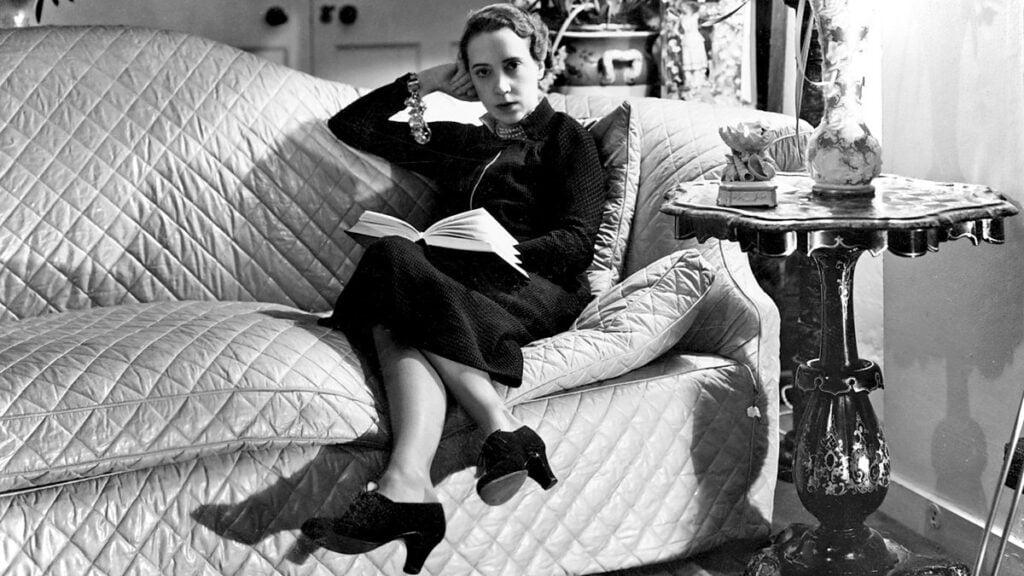 A photography of Elsa Schiaparelli reading a book.