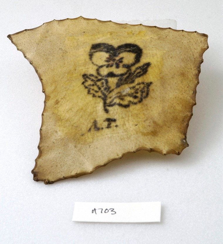 Tattoos history, art & culture: Tattoo fragment showing flower and initials,