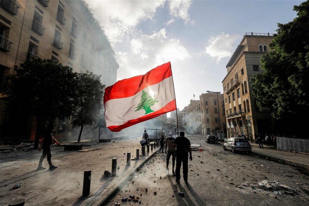Photograph of a protestor carrying the Lebanese flag through a rubble-strewn Beirut street.