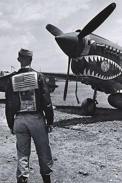 Photo of an American pilot standing in front of the Curtiss P-40.