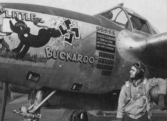 """Major R.G. Rogers of the 367th FG photographed looking at his P-38 Lightning aircraft """"Little Buckaroo""""."""