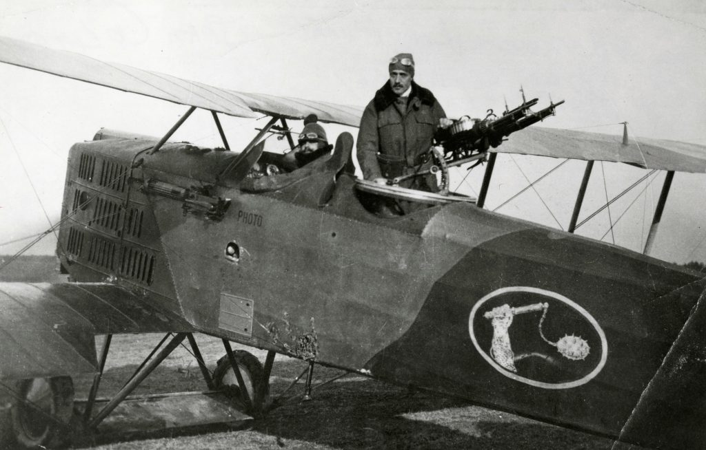 Lieutenant Godillot in front cockpit and Lieutenant Jean Columany standing in rear cockpit of Breguet 14A2, France, 1917-1918. Emblem on side aircraft shows a mailed fist holding a military flail.