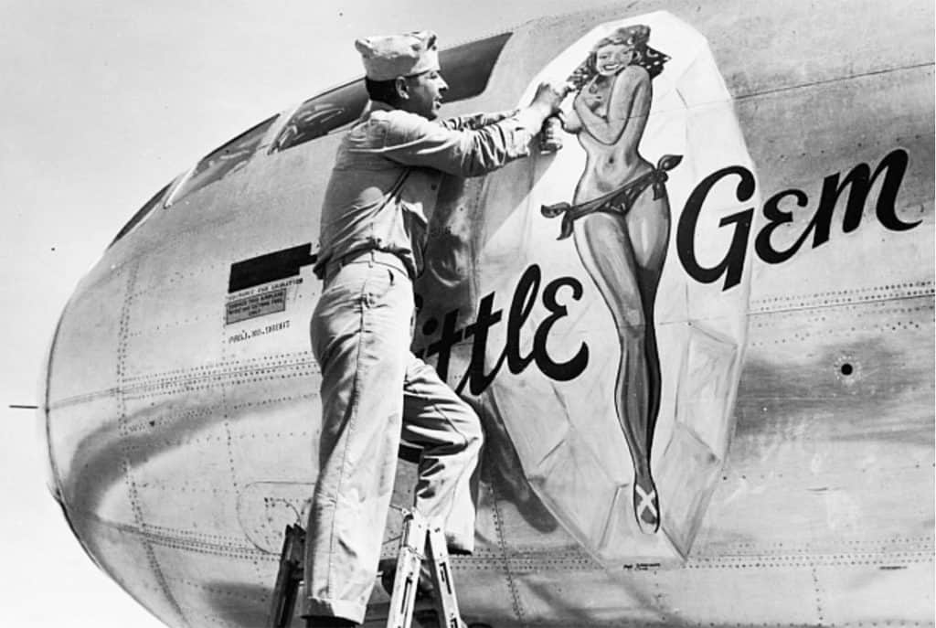 """U.S. Marine Randall Sprenger putting the finishing touches on Boeing B-29 Superfortress with """"Little Gem"""" Nose Art."""