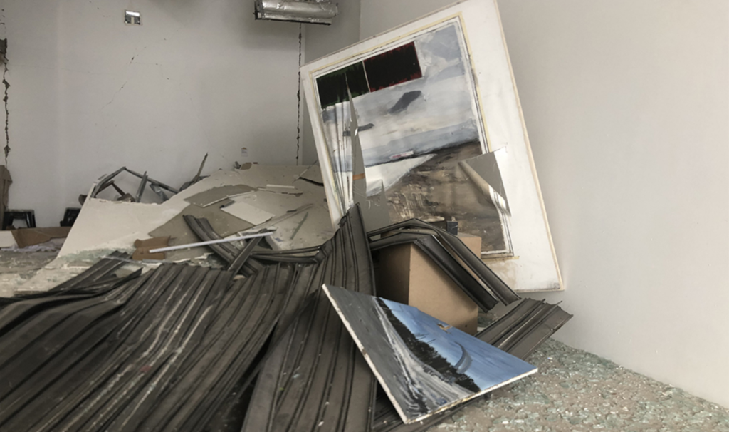 Photograph of internal damages at Marfa Gallery showing paintings blown from the walls, shattered glass, and other debris littering the floor.