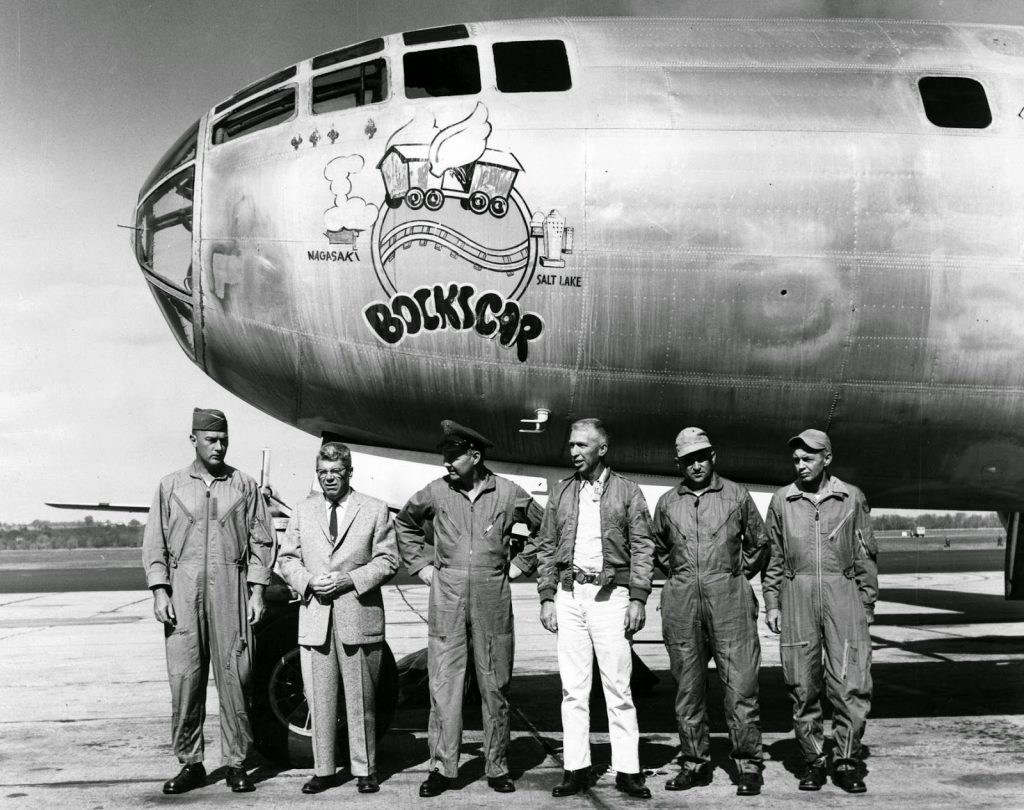 """Crew members standing in front of the B-29 Bockscar Superfortress which dropped the atomic bomb """"Fat Man"""" on Nagasaki, Japan."""
