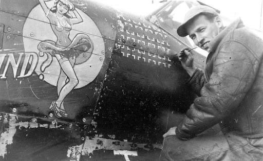 """Nose Art artist Dan Allen painting one of the 15 victories credited to Lt. Nicholas """"Cowboy"""" Megura on the """"Ill Wind?"""" a P-51 Mustang in the 334th Fighter Squadron."""