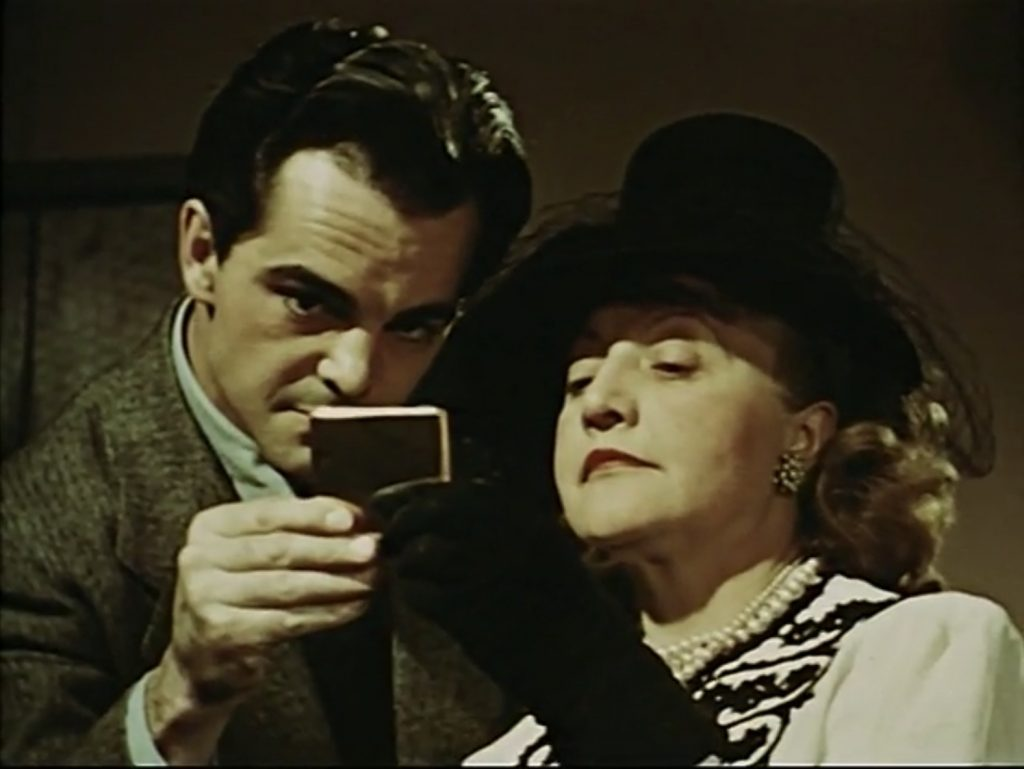 """Mrs A and Joe looking at the mirror, """"Ruth, Roses and Revolvers"""" scene from Dreams that money can buy movie, 1947."""