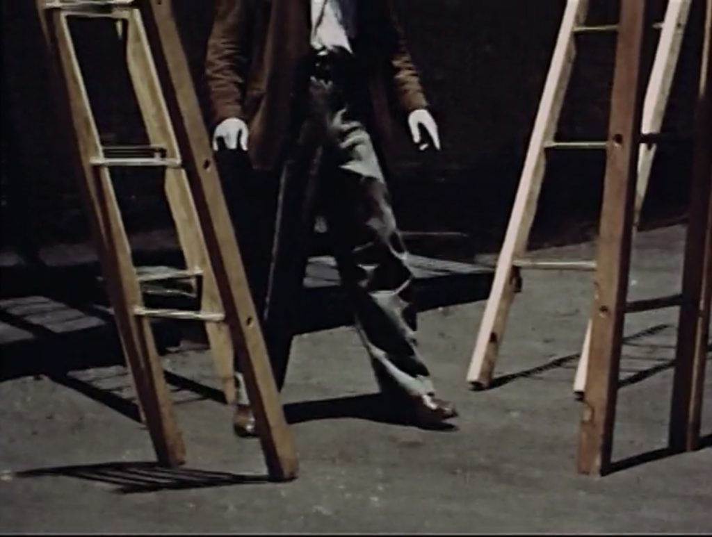 """Joe standing in front of the ladders leading up in four different directions, """"Narcissus"""" scene from Dreams that money can buy movie, 1947."""