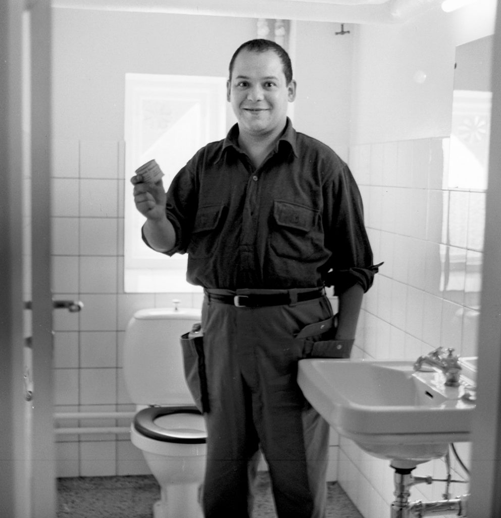 Toilet art: Piero Manzoni photographed in the bathroom and holding in hand his Merde d'artiste, 1961. Source: www.artesvelata.it.